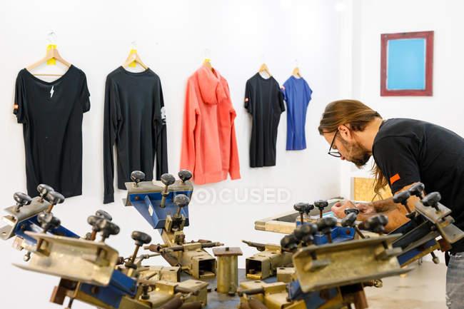 Сконцентрований чоловік-художник у брудному фартусі, працює з кремом срібла, створюючи друк на футболках у майстерні. — стокове фото