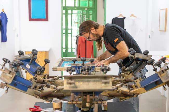 Artiste masculin concentré sur un tablier sale travaillant avec sérigraphie tout en créant des imprimés sur des t-shirts en atelier — Photo de stock