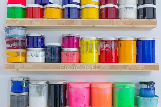 Полки с разноцветными банками краски различного размера и цвета на рабочем месте — стоковое фото