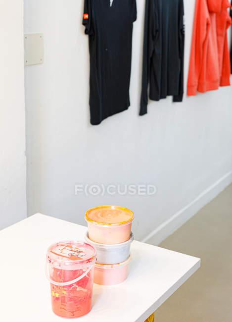 Стол с мягкими цветными баночками краски различной формы и цвета на рабочем месте — стоковое фото