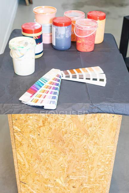 Paleta colorida y diferentes pinturas para imprimir en taller de trabajo. - foto de stock