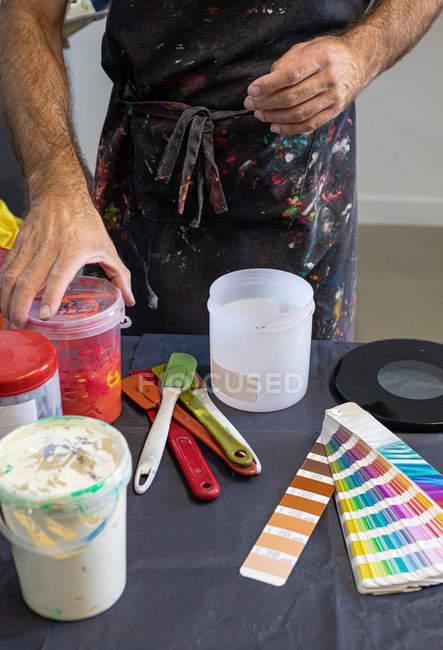 Erntehelfer in schmutziger Schürze bereitet in Werkstatt verschiedene Farben für Siebdruck vor — Stockfoto