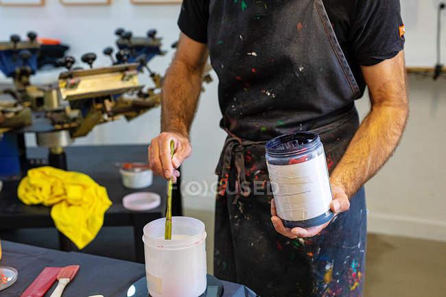 Сконцентрований урожай у брудному фарбі, що змішує різні фарби для серирафії у майстерні. — стокове фото
