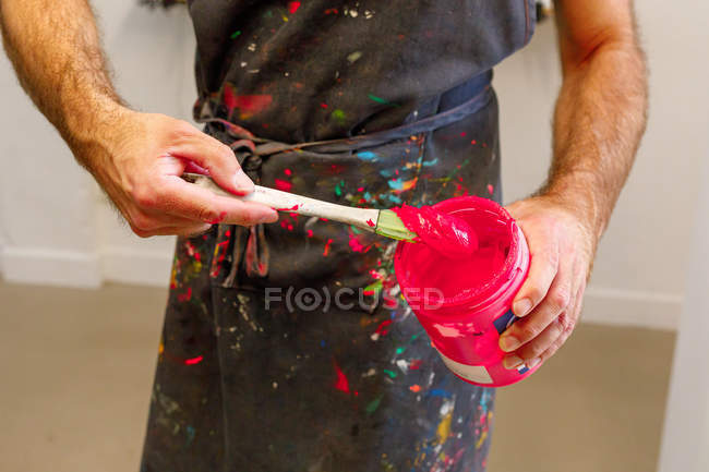 Concentrated crop man wearing dirty apron mixing various paints for serigraphy in workshop — Stock Photo