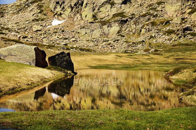 Petit lac au fond d'une montagne rocheuse avec neige en Sierra de Guadarrama Espagne — Photo de stock