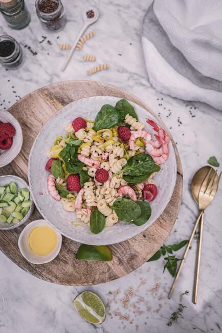 Сверху аппетитный салат и ягоды соуса нарезанные известью на деревянном стенде с солью и перцем на столе — стоковое фото