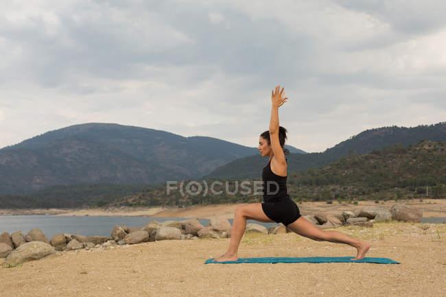 Женщина, занимающаяся йогой на открытом воздухе в облачный день на пляже Дам — стоковое фото