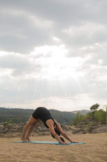 Взрослая женщина в позе собаки вниз головой, занимаясь йогой на открытом воздухе на дамбе. — стоковое фото