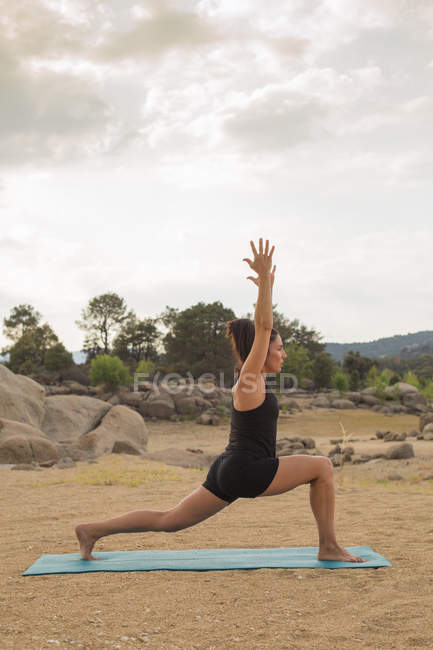Взрослая женщина в глубокой позе, занимающаяся йогой на открытом воздухе на пляже Дам. — стоковое фото