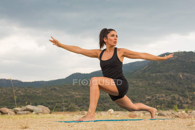 Mujer adulta media estirándose mientras hace yoga al aire libre en la playa de la presa - foto de stock