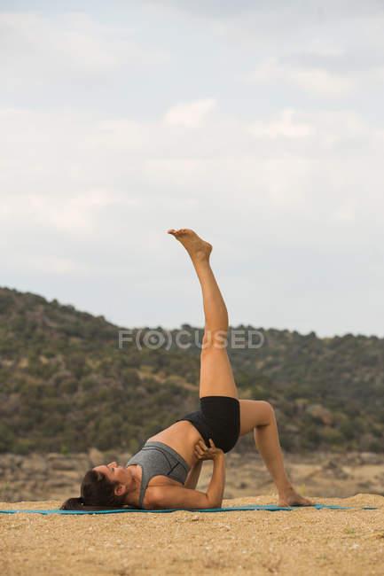 Взрослая женщина с ногами, занимающаяся йогой на открытом воздухе на дамском пляже — стоковое фото