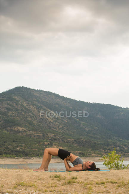Mid adult woman in bridge pose doing yoga outdoors on dam beach — Stock Photo