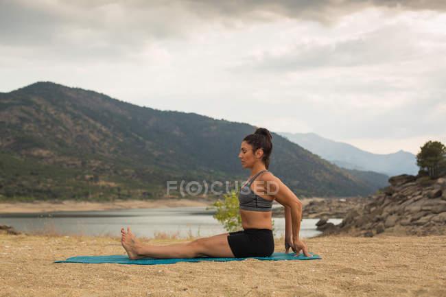Mujer adulta haciendo yoga al aire libre en la playa de la presa — Stock Photo