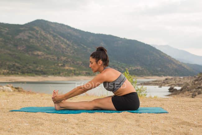 Femme adulte mi-flexion tout en faisant du yoga en plein air sur la plage du barrage — Photo de stock