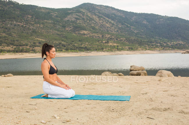 Mid adult woman in hero pose doing yoga outdoors on dam beach — Stock Photo