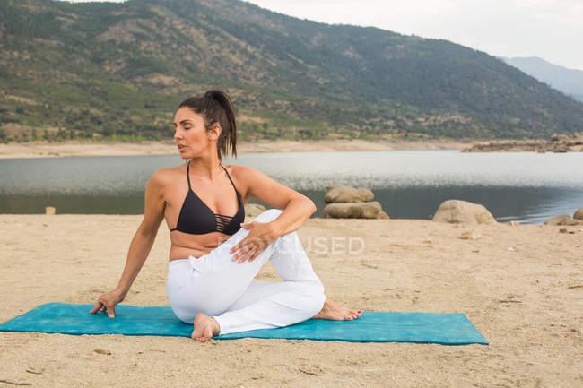 Mid adult woman doing yoga outdoors on dam beach — Stock Photo