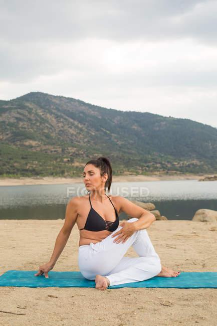 Взрослая женщина, занимающаяся йогой на открытом воздухе на пляже Дам — стоковое фото