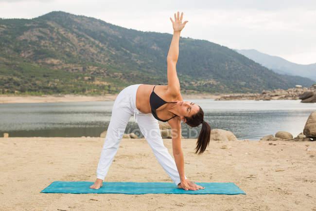 Mujer adulta en posición triangular haciendo yoga al aire libre en la playa de la presa — Stock Photo