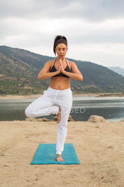 Mujer adulta en pose de árbol haciendo yoga al aire libre en la playa de la presa — Stock Photo