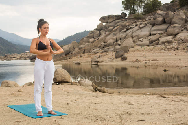 Mid adult woman doing yoga outdoors on dam beach — Stock Photo