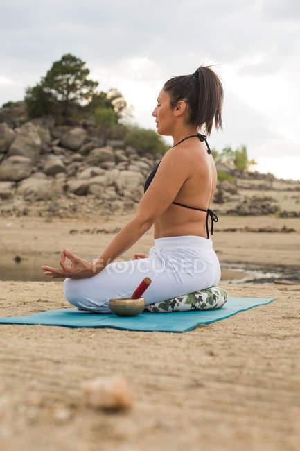 Взрослая женщина медитирует в позе йоги лотоса на открытом воздухе на пляже Дам — стоковое фото