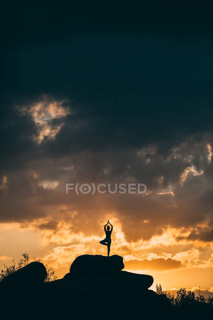 Silhouette of woman doing yoga tree pose outdoors at sunset — Stock Photo