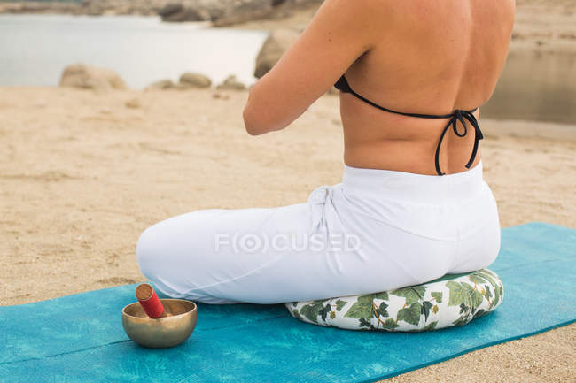Cropped view of woman meditating in lotus yoga pose outdoors on dam beach — Stock Photo