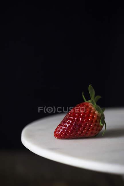 Fresa madura dulce sobre plato blanco sobre fondo negro - foto de stock
