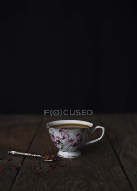 Маленькая ложка с измельченным шоколадом, помещенная рядом с чашкой горячего кофе на деревянном столе на черном фоне — стоковое фото