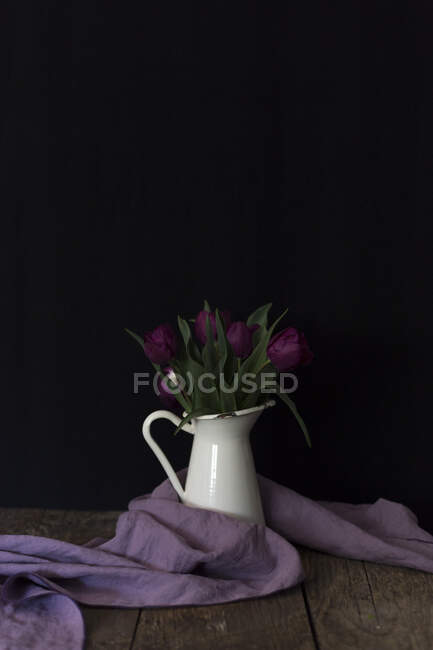 Tiny metal bucket with bright purple flowers placed on lumber tabletop — стокове фото