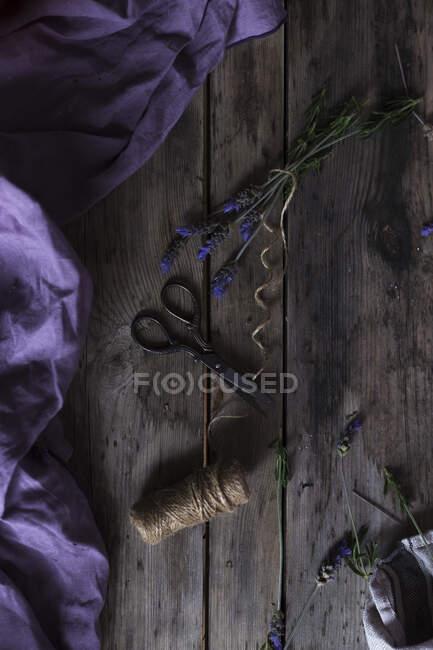 Dall'alto corda di lino e forbici vintage posizionate su un tavolo in legno vicino a tessuto viola e lavanda fresca — Foto stock
