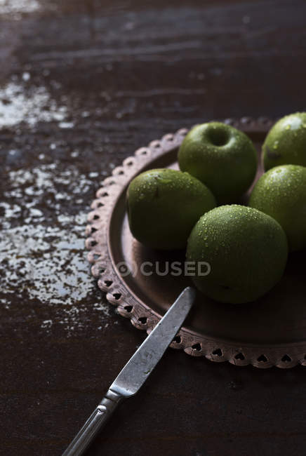 Plate of wet green fresh apples on shabby wooden table with knife — Stock Photo