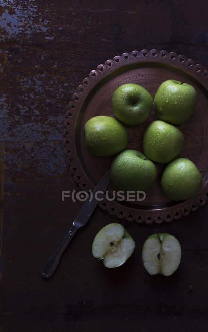 Teller mit frischen grünen Äpfeln auf schäbiger dunkler Tischplatte mit Messer — Stockfoto