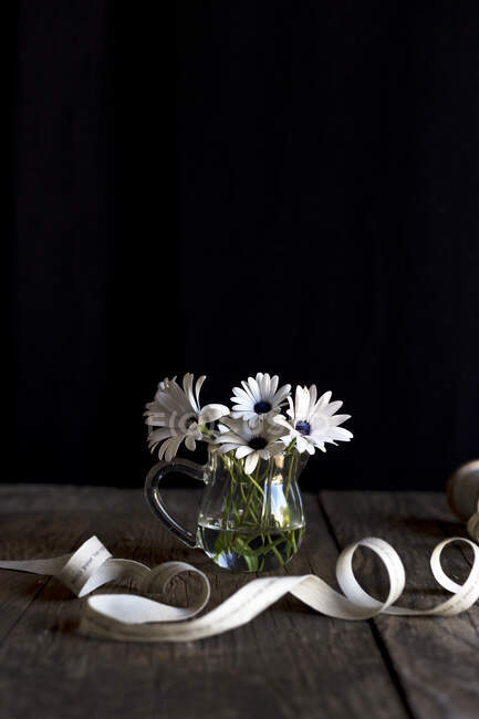 Coiling ribbon placed on timber tabletop near glass vase with white flowers on black background — Stock Photo