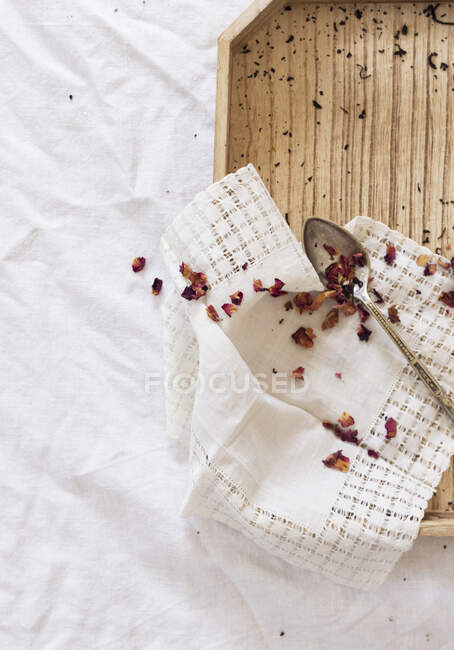 From above dried tea leaves and aromatic petals placed on napkin and tray over white fabric — Stock Photo