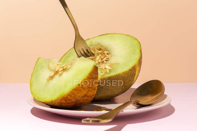 Corte melón dulce maduro en el plato con cuchara y tenedor en la mesa rosa - foto de stock