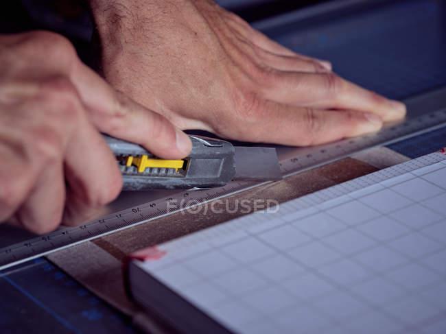 Безликий человек работает в букмекерской мастерской и измеряет обложку книги карандашом и линейкой — стоковое фото