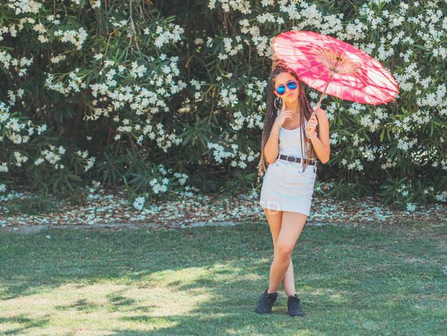 Стройная молодая женщина в летней одежде с зонтиком стоя ноги скрещены возле цветущих деревьев — стоковое фото
