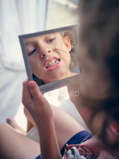 Отражение в квадратном зеркале лица малыша с бинтом на щеке, изучающего молочный зуб с открытым ртом в комнате — стоковое фото