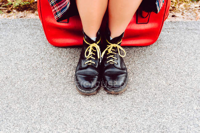 Legs of woman in black shiny boots with yellow shoelaces sitting on red suitcase waiting for transport on road — Stock Photo