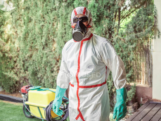 Fumigator in respiratory mask and white uniform for fumigation ready for disinfection plants in yard — Stock Photo