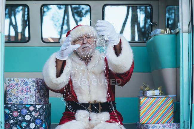 Старший чоловік в костюмі Діда Мороза сидить у ретро-фургоні між подарунками і проведенням гірляндою в Умілі руках — стокове фото