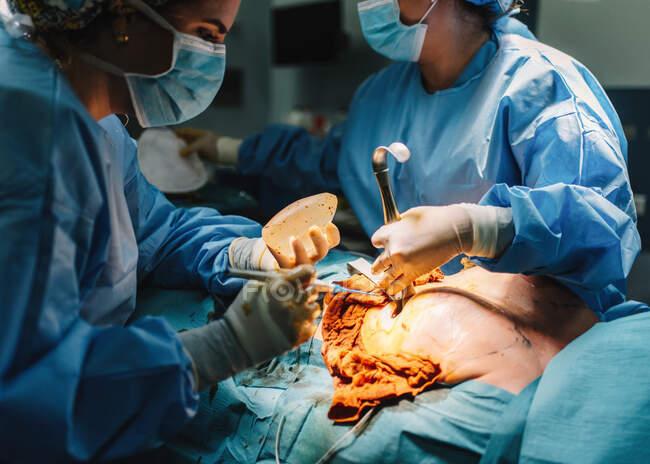 Unbekannter Chirurg operiert mit Instrumenten und Erntehelferin — Stockfoto