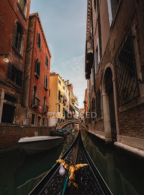Ornamental beak of gondola floating down narrow channel with old stone houses on sides — Stock Photo