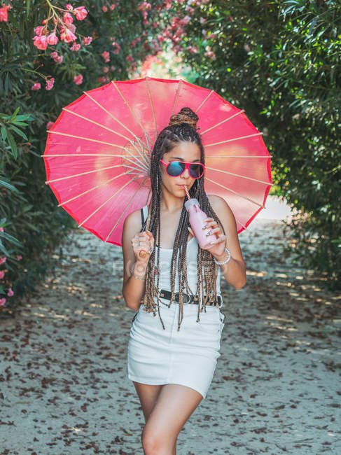 Slim young woman in summer outfit with umbrella drinking beverage near blooming trees — Stock Photo