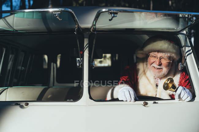Homme âgé souriant en costume du Père Noël conduisant vieux van avec cloche en métal à la main le jour ensoleillé — Photo de stock