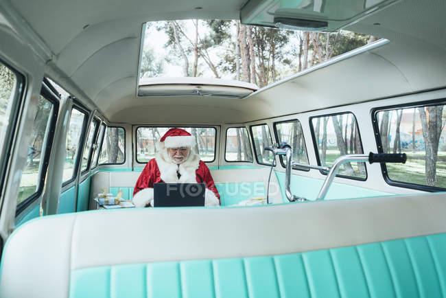 Весела людина в костюмі Діда Мороза сидить у фургоні з ноутбуком і яскравими подарунками — стокове фото
