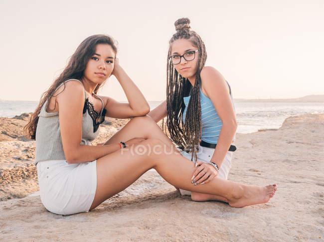 Smiling trendy young women relaxing on seashore — Stock Photo