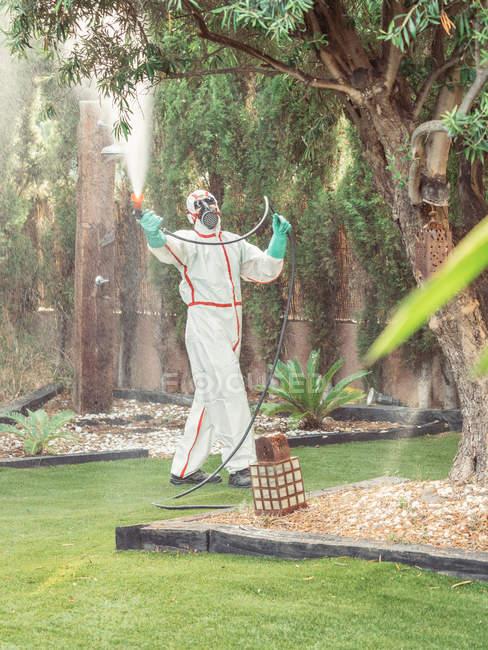 Fumigator in white uniform spraying substance on garden — Stockfoto