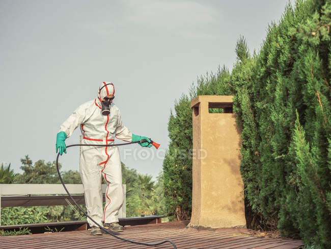 Specialist in uniform for fumigation holding hose analyzing distance for disinfection — Stock Photo